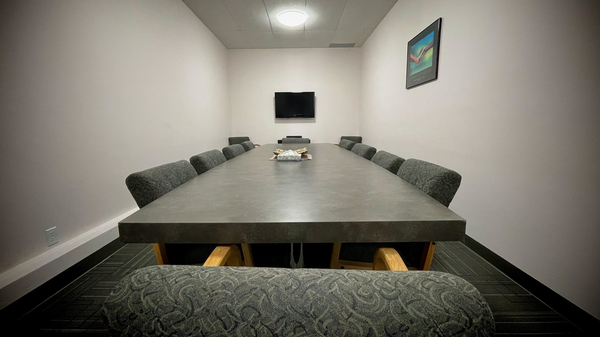 A board room table looking from the head of the table down the middle to a wide screen tv on the wall.