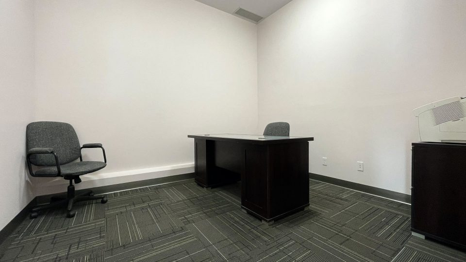 A spacious, clean office, complete with desk and chest of drawers.